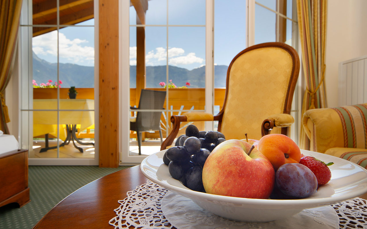 Close-up of a plate with fruit in a room at the Hotel Kristall in South Tyrol with balcony in the background