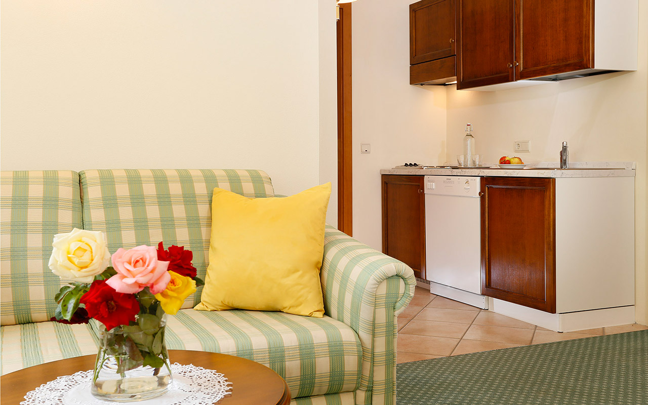 Close-up on the sofa and on the coffee table and little kitchen in the background: an apartment at the Hotel Kristall