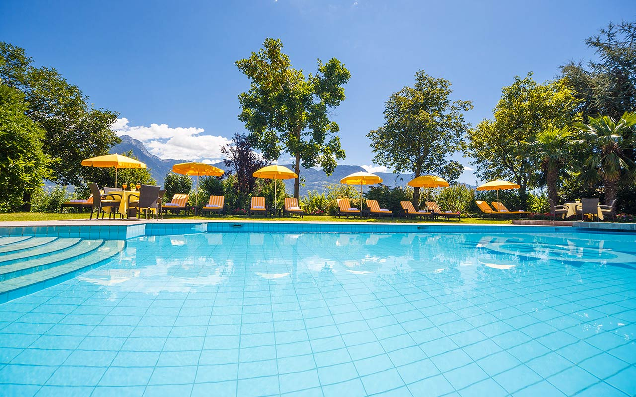 Outdoor pool with beach umbrellas and deck chairs at the hotel Kristall in Marling in a sunny day
