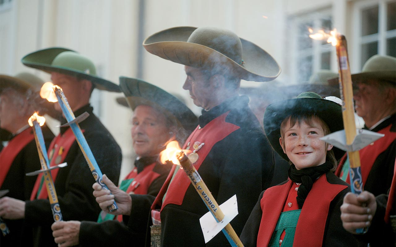 People in South Tyrolean costumes with lighted candles