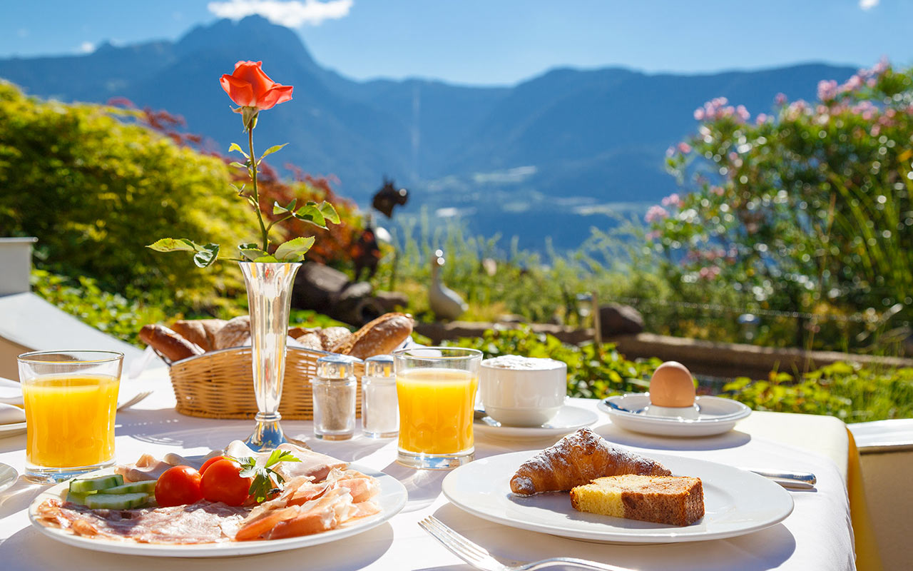 Close-up of dishes with meats, breads, desserts and two glasses of orange juice on a table out in the veranda at hotel Kristall, South Tyrol