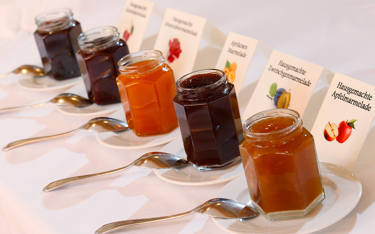 Five different jam jars with spoons: breakfast at hotel Kristall