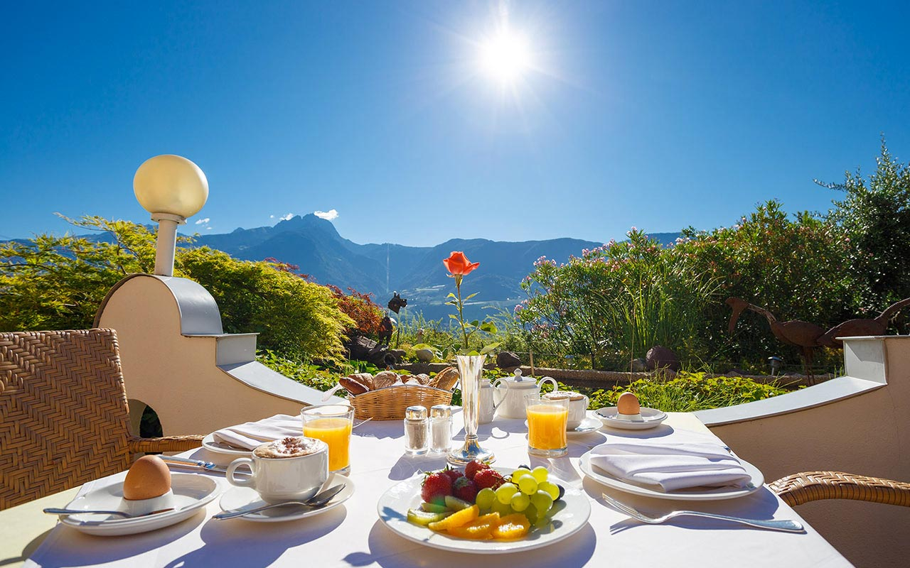 Outdoor table set for breakfast at the Hotel Kristall on a sunny day