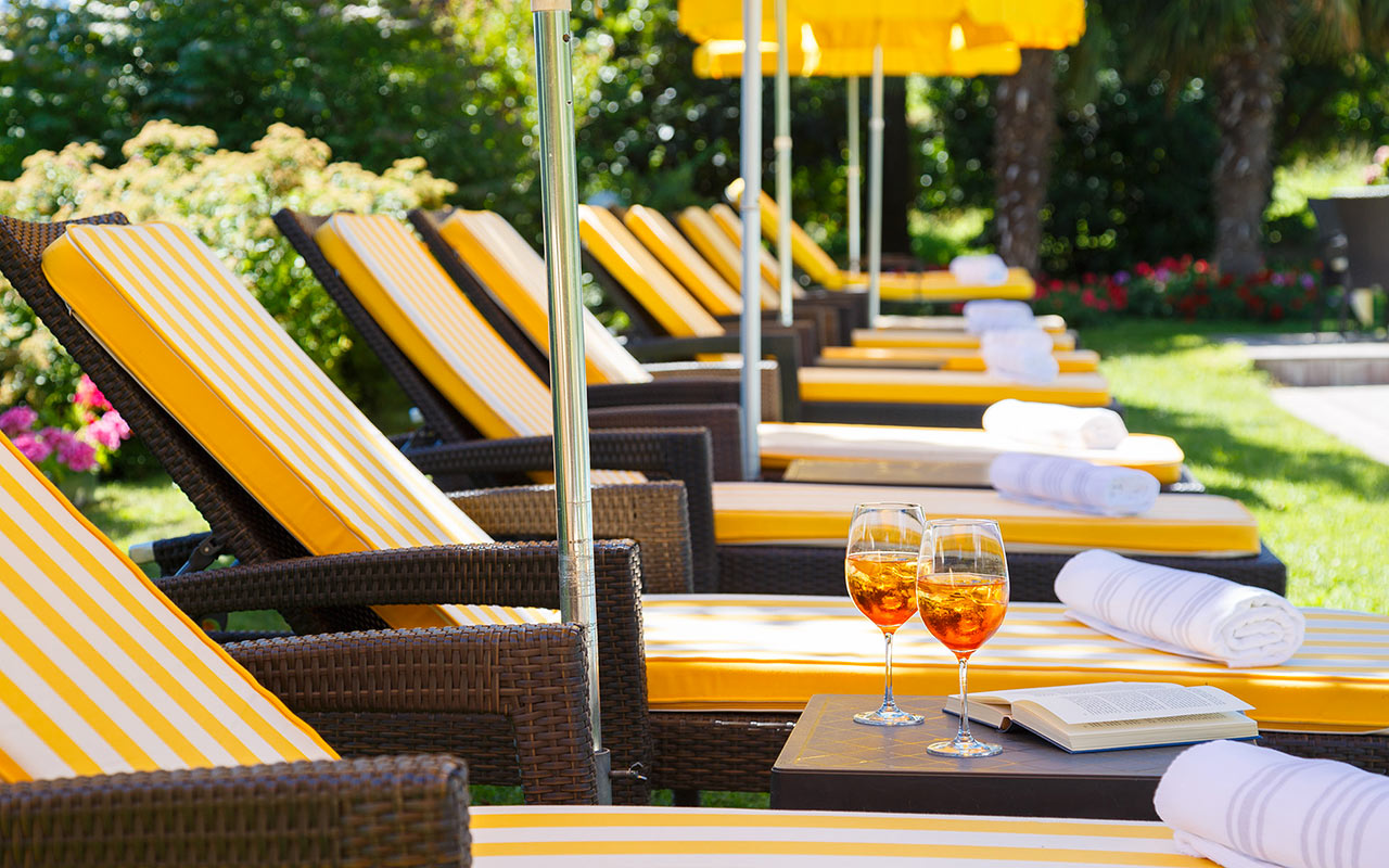 Row of beach chairs and umbrellas in the garden with two drinks on the table