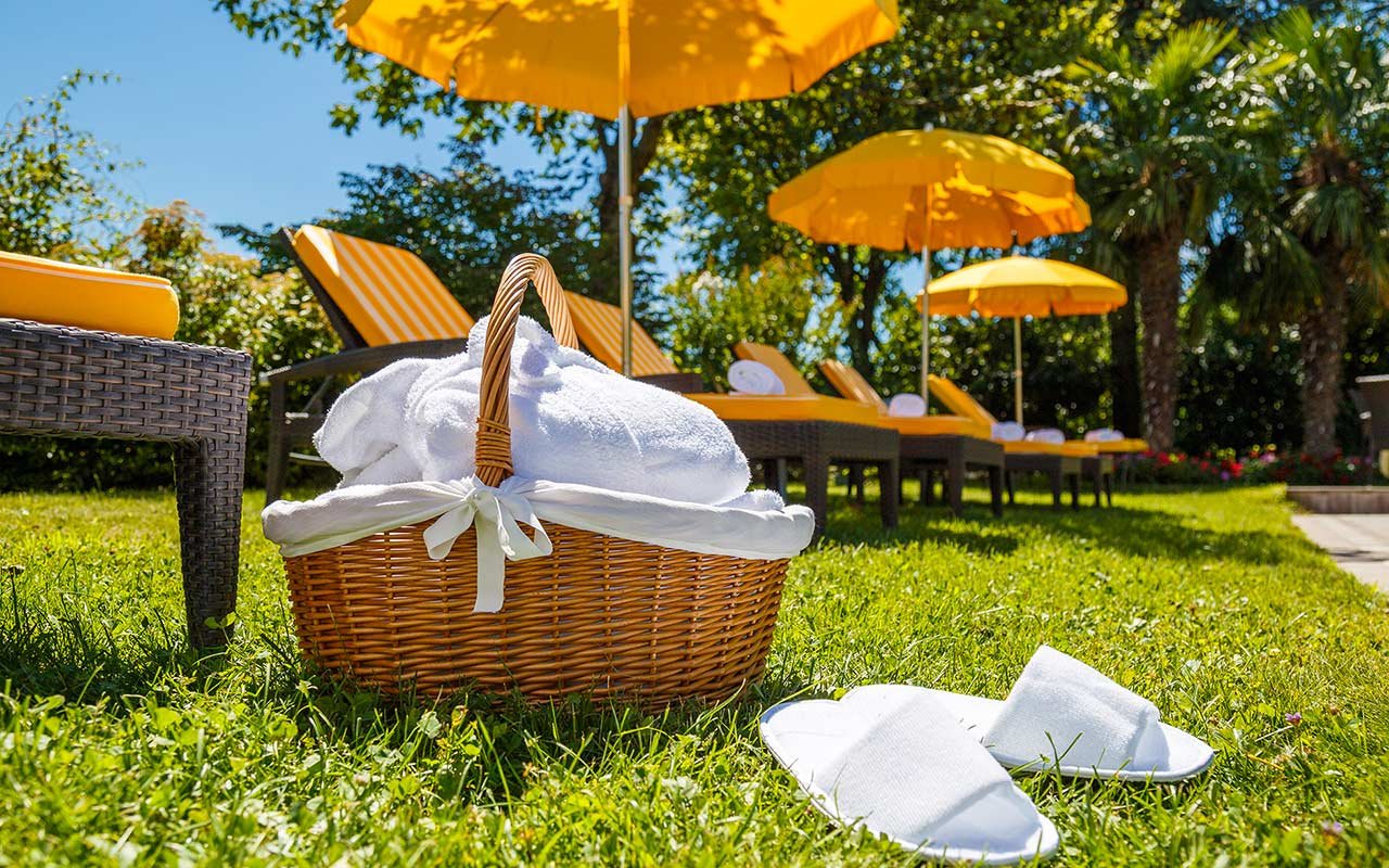 Basket with towels and slippers in the garden with deck chairs and beach umbrellas at the Hotel Kristall, South Tyrol