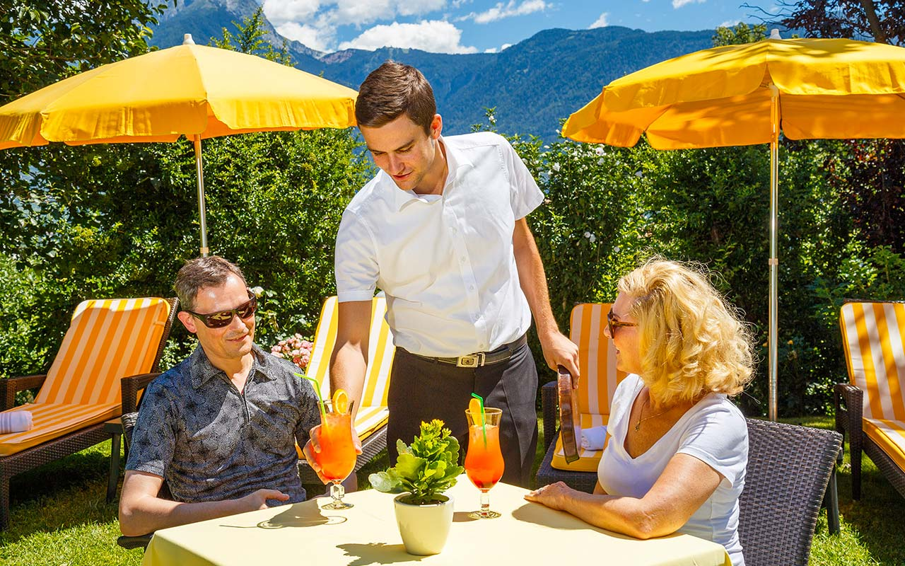 Waiter brings two cocktails for a couple sitting around an outdoor table on a summer day