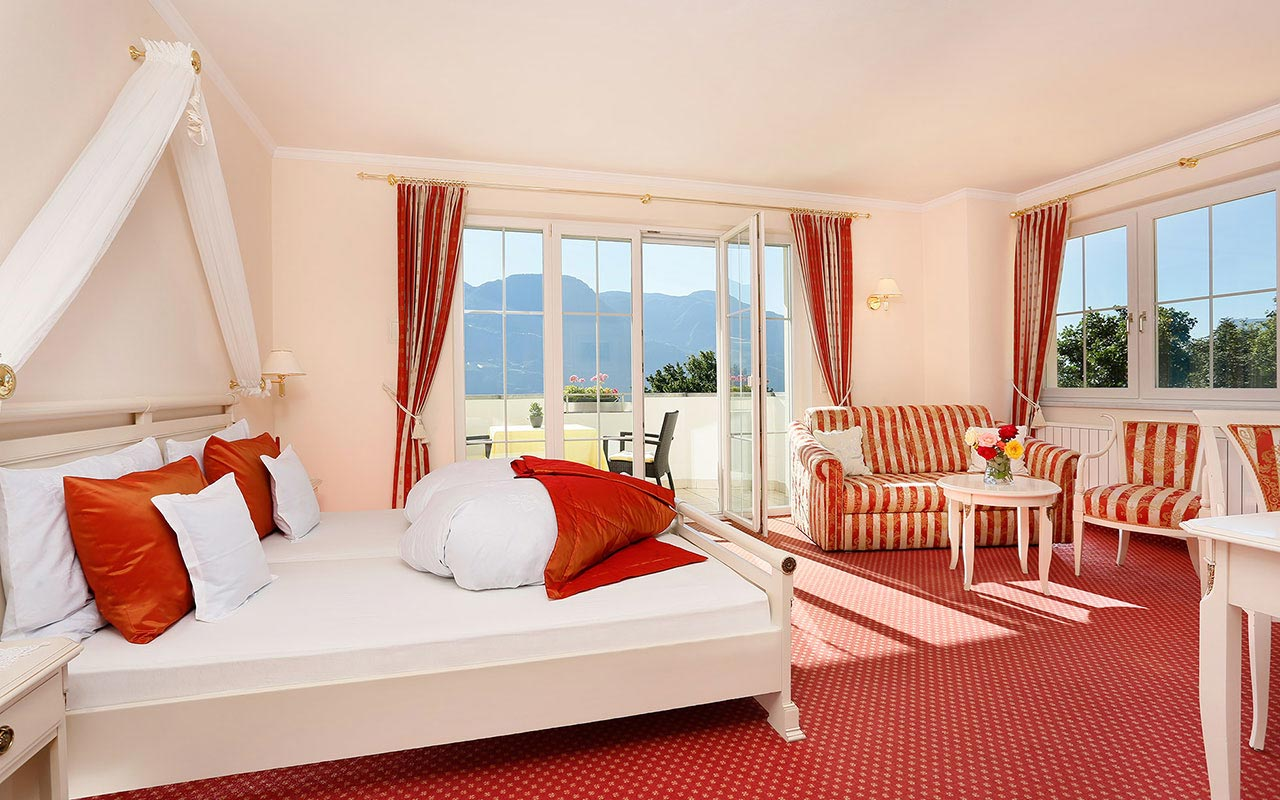 Bright double room with red carpet, balcony and window at the Hotel Kristall near Merano